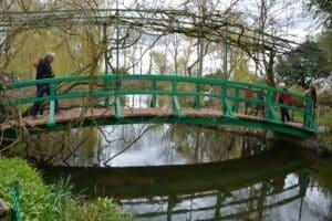 Der Maler Monet hat einen Garten mit Seerosenteich angelegt. Eine kleine Bogenbrücke verbindet die beiden Seeufer und spiegelt sich im Wasser.