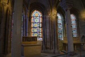 Im Innenraum der Kirche St. Denis wird der Blick zwischen Säulen und Bögen auf drei Fenster im Hintergrund gelenkt. Sie leuchten hell und farbig. Die Lichtreflexe auf dem Mauerwerk und den Säulen geben der Atmosphäre etwas Unwirkliches und Geheimniosvolles. Ein Steinaltar steht vorne.