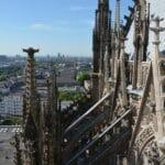 Im Bildvordergrund sind steinerne Türmchen des Kölner Doms zu sehen. Der Standort des Betrachters ist hoch. Gemauerte Stützen und ein Teil des Domdachs sind rechts zu sehen. Im Bildhintergrund fällt der Blick vor blauem Hintergrund bis ins Umland.