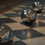 Drei silbern glänzende Metallkugeln liegen auf einem Steinfliesenboden. Auf den Oberflächen der Kugeln spiegeln sich der Raum und Menschen. Die glänzenden Kugeln inspirieren bei der Kunstbetrachtung die eigenen Gedanken.