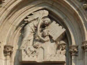 Eine Skulptur aus Stein über einem Kirchenportal zeigt einen sehr großen Engel. Mit einer Hand kippt er einen großen Turm zur Seite. Die andere Hand reicht er dem Menschen, der aus dem Turm befreit ist. Im Team kann große Dynamik entstehen und Unmögliches möglich werden.
