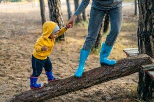 Ein kleines Kind geht erste Schritte auf einem Baumstamm. Halt gibt die Hand eines Erwachsenen, der auch auf dem Baumstamm steht.
