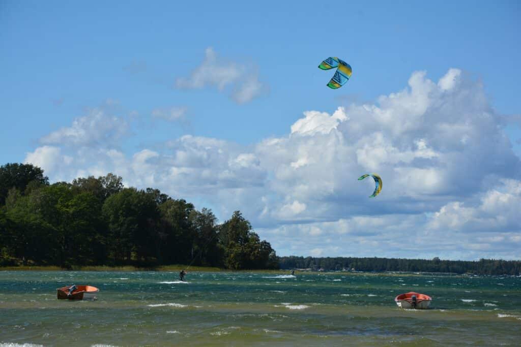 Kitesurfen vor blauem Himmel auf stürmischem Wasser.