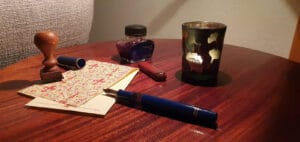 Briefpapier auf einem Tisch, ein Füller, ein kleines Tintenfass und eine Kerze vermitteln eine ruhige Atmosphäre zum Nachdenken und Schreiben