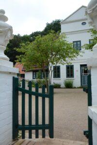 Das Törchen eines grünen Gartenzauns ist geöffnet und gibt den Blick auf ein weißes Haus mit Haustür und Fenstern frei. Die Atmosphäre ist einladend und inspirierend