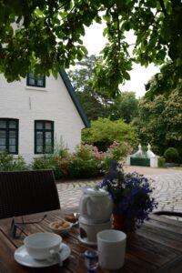 Im Bildvordergrund steht ein Teegedeck auf einem Holztisch unter einem Laubbaum. Zwei Stühle kennzeichnen den Ort des Gesprächs. Im Hintergrund steht ein weißes Haus mit vielen Fenstern und einem bunten Blumenbeet davor. Der Ort strahlt Ruhe aus.