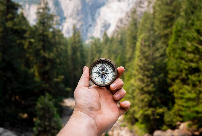Ein Kompass wird in einer Hand gehalten vor einem Tal im Gebirge