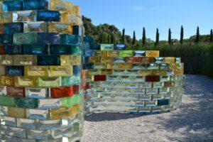 Eine aus farbig schillernden Glasbausteinen gebaute Mauer verläuft in großen Wellenlinien. So ist man eingeladen, an dieser Wand entlang ein Wegstück in der Natur zu gehen.