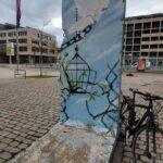 Ein Stück der Berliner Mauer ist mit einer Friedenstaube bemalt, die Eisenketten davonfliegt. Der Zaun ist offen, die Zweige grünen.