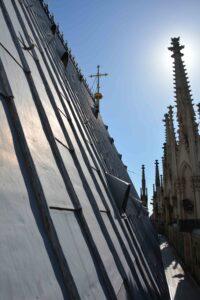 Das Bild zeigt eine große graue Dachfläche des Kölner Domes. Vor blauem Himmel sind kleine Türmchen zu sehen. Die Sonne steht hinter einem kleinen Schmuckturm und überstrahlt ihn.