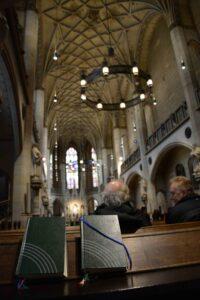 Kircheninnenraum der Schlosskirche mit zwei geschlossenen Büchern auf der Bank im Bildvordergrund. Dahinter in Rückenansicht zwei Männer sitzend im Gespräch. Lichterkronen und Fenster sind helle Lichtpunkte in der weiten Kirchenhalle.