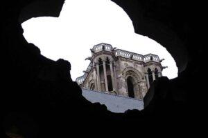 Ein Kirchturm ohne Spitze ist aus Untersicht in der Bildmitte zu sehen. Er wird eingerahmt von einer dunklen Silhouette eines Kleeblatts.