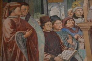 Der Bildausschnitt eines Wandgemäldes zeigt die Gesichter von gelehrten Männern, deren Blicke in verschiedene Richtungen gehen: im Gespräch, mit einem Buch befasst, offenbar hörend auf eine Stimme außerhalb des Bildraumes. Es ist Treffen von Menschen, die miteinander etwas beraten und entscheiden wollen.