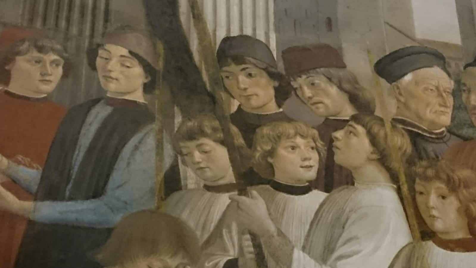 Der Bildausschnitt eines Wandgemäldes zeigt die Gesichter von Kindern, jungen Männern und älteren Menschen, die einander etwas mitteilen. Die jungen Menschen schauen interessiert und fragend.